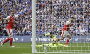 Arsenal's Alexis Sanchez, right, scores past Chelsea goalkeeper Thibaut Courtois.