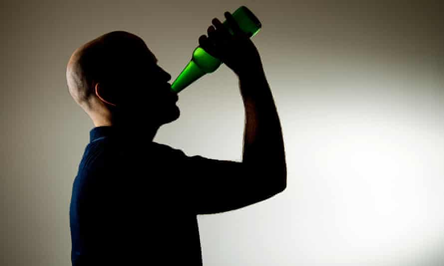 A man downing a bottle of beer