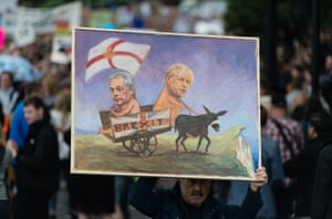 A protester holds a cartoon painting of leave campaigners Nigel Farage and Boris Johnson