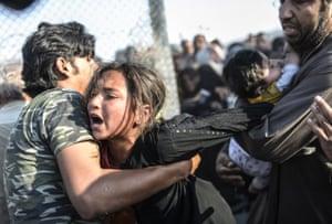 Syrians fleeing the war rush through broken down border fences to enter Turkish territory illegally, near the Turkish border crossing at Akcakale.