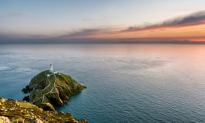 South Stack lighthouse in Holyhead, Anglesey, North Wales. The lighthouse sits on top of a rock island with white walls which lead people to the lighthouse. The photograph was taken on a summer evening with a beautiful orange sunset on the horizon.
