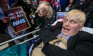 A Boris Johnson impersonator lies in a makeshift hospital bed next to an effigy of Theresa May during a demonstration in London on Saturday.