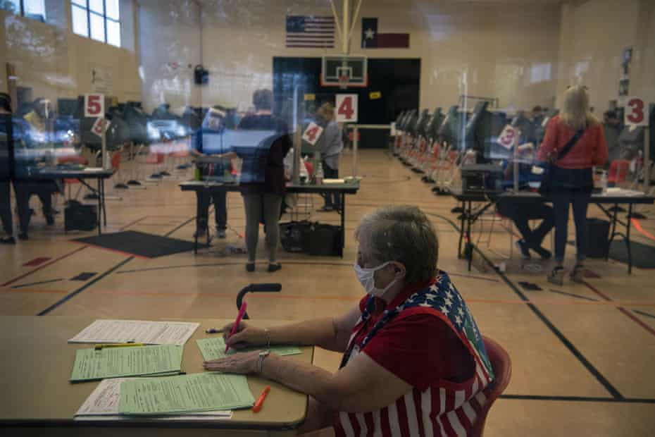An election worker handles paperwork as voters cast ballots at an early voting polling location for the 2020 Presidential elections in Houston, Texas, U.S., on Tuesday, Oct. 13, 2020.