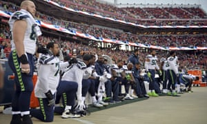 Seattle Seahawks players sit and kneel during the playing of the national anthem on Sunday