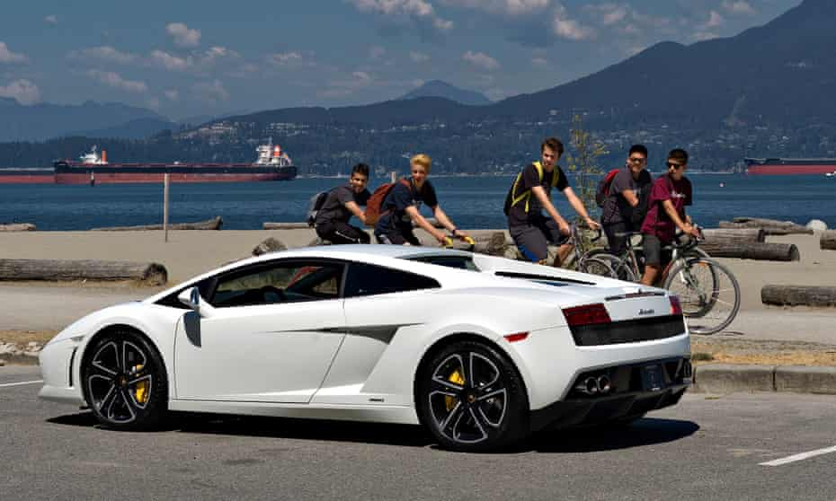A group of young men look at a Lamborghini sports car stopped in a waterfront park in Vancouver.