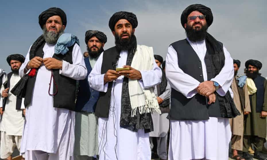 Taliban spokesman Zabihullah Mujahid (centre) speaking at Kabul airport, 31 August 2021.