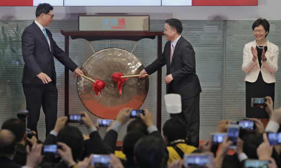 Hong Kong's new chief executive Carrie Lam claps hands as People's Bank of China's Pan Gongsheng and Monetary Authority's Norman Chan beat a gong to launch Bond Connect.