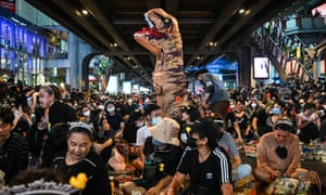 Students, including one in a dinosaur costume, gather for a pro-democracy protest in central Bangkok.