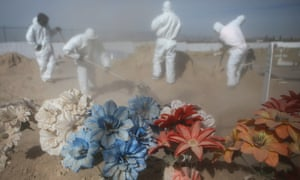 Cemetery workers in personal protective equipment shovel dirt as they bury a victim of Covid-19 at Sueños Eternos cemetery in Ciudad Juarez, Mexico.