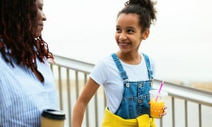 Happy mother and daughter holding orange juice and coffee walking outdoors