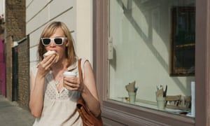 A young woman in the street eating what looks like a cupcake, and holding a cup of coffee.