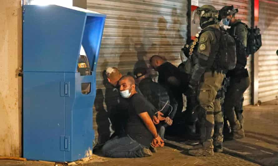 Israeli forces detain a group of Arab-Israelis in the mixed Jewish-Arab city of Lod.