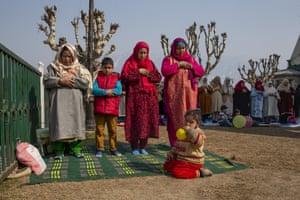 Kashmiri Muslim devotees pray as a young girl blows air into a balloon during special prayers on the death anniversary of Abu Bakr Siddiq, the first Caliph of Islam, at Hazratbal Shrine near Shrinagar