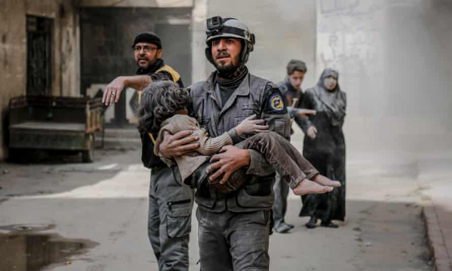 A rescue worker carries a girl who was found alive inside the debris of buildings in eastern Ghouta.
