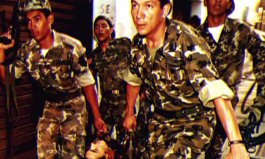 Soldiers loyal to President Carlos Andres Pérez carry a comrade's body after he was killed by rebels