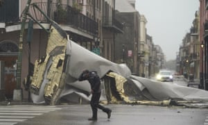 A man passes by a section of roof that was blown off a building in the French Quarter by fierce winds on Sunday