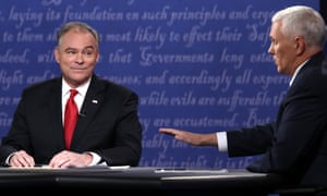 Tim Kaine listens as Mike Pence speaks.