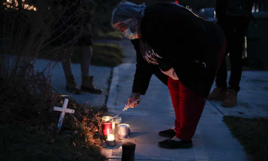 A neighbor lights a candle at a small memorial near the site of the fatal police shooting of Andre Hill by police in Columbus, Ohio.
