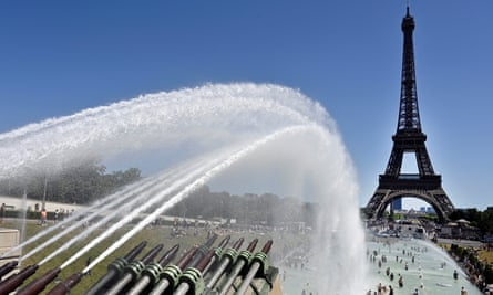 People cool down in the fountains near the Eiffel Tower in Paris during the June heatwave.