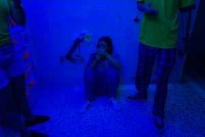 Maria Laura, 18, sits on the floor at party she has organised with her friends