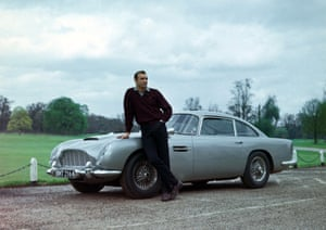 Leaning on an Aston Martin DB5 as Bond in Goldfinger (1964).