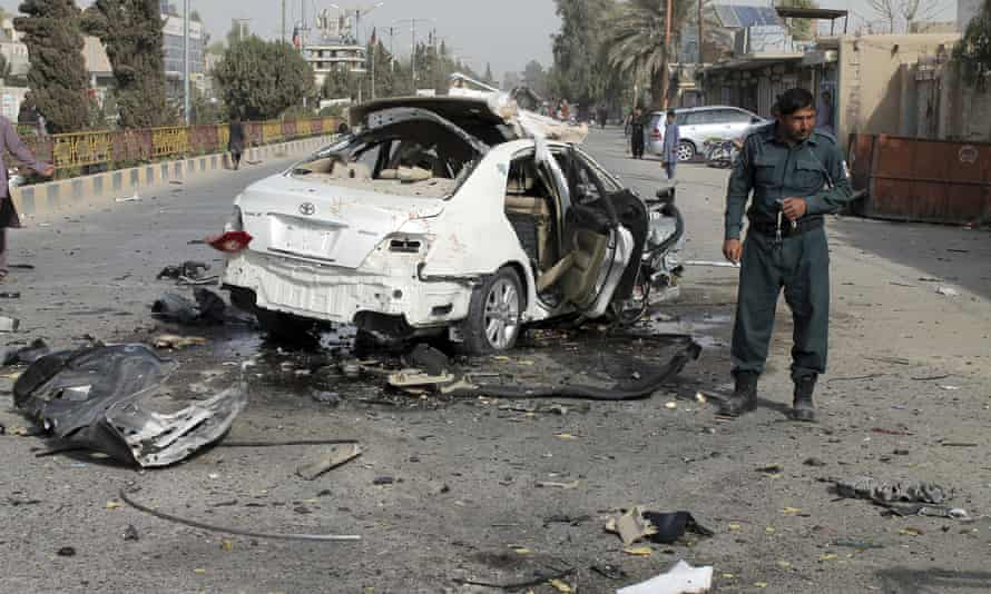 An Afghan police officer investigates a car damaged in a bomb attack in Helmand