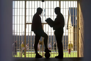 A custody officer speaks to a young offender before a football match at a youth prison