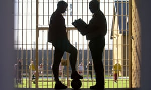A prison officer talks to a young offender before a football match.