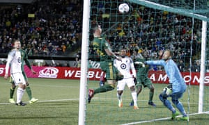 Portland Timbers' Lawrence Olum watches in the background as his shot loops up into the net.