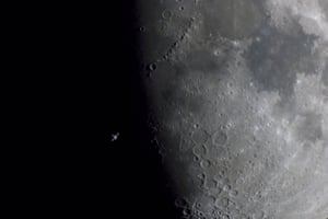 The tiny insect-like International Space Station caught as it crosses the face of the moon.