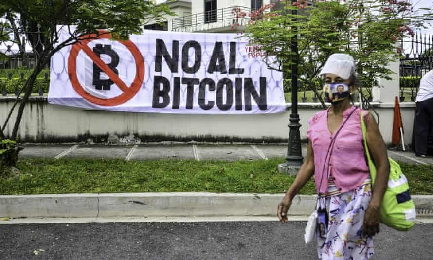 """A woman walks by a banner reading """"No to Bitcoin"""" during a demonstration in el salvador"""