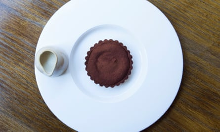 A large round white plate with a chocolate tart in a round, scalloped case in the middle and a small white jug on the edge