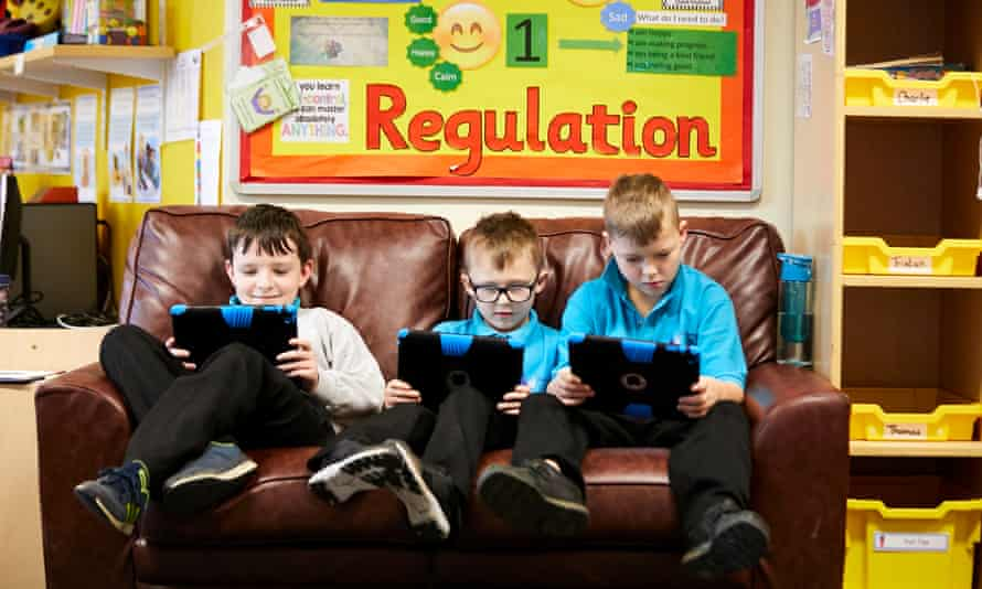 Children sitting on sofa reading from tablet computers