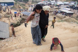 A boy helps a woman up some steps in Kutupalong camp