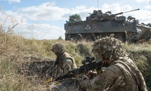British infantry personnel on a training exercise with armoured vehicle in the background.