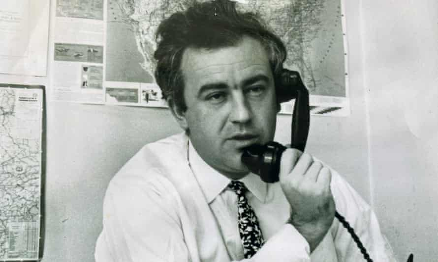 Black and white photo of Godfrey Hodgson on the phone, with maps pinned on the wall behind him