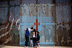 A family talks with relatives through the border fence between Mexico and the United States in Playas de Tijuana