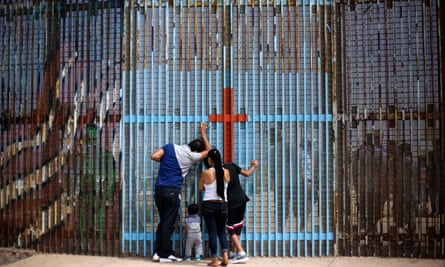 A family talks with relatives through the US-Mexico border fence in Tijuana, Mexico. The Trump administration has unveiled sweeping measures to deport millions of undocumented people.