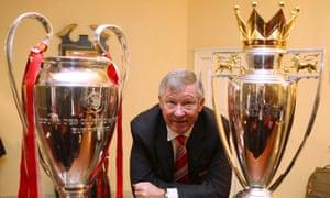 Sir Alex Ferguson dengan trofi UEFA Champions League dan FA Barclays Premier League pada tahun 2008