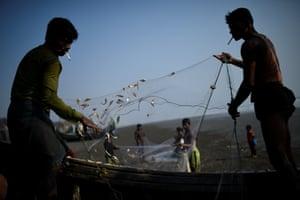 Rohingya refugees shake out freshly caught fish from nets on Shamlapur beach