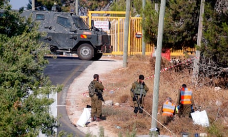 Forensic experts inspect the scene where the body of an Israeli soldier was found with multiple stab wounds near the settlement of Migdal Oz in the West Bank