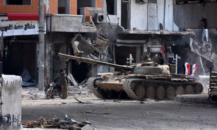 Syrian government troops patrol the al-Shaar neighbourhood after taking control of the area in Aleppo, Syria.