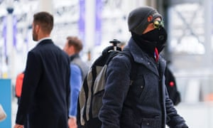 A man wearing protective face mask walks through Waterloo station in London.