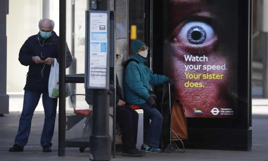 People wearing face masks as they wait at a bus stop in London.