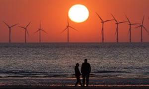 The sun sets behind the wind turbines of Burbo Bank Offshore Wind Farm in the Irish Sea.