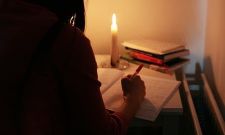 Woman in silhouette working by candlelight