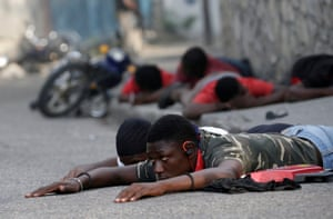 Protesters lie on the ground after being detained by police during clashes at a demonstration called by opposition parties against the government, in the streets of Port-au-Prince.