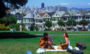 Two hippies play guitar in a San Francisco park.