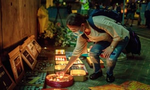 A pro-democracy supporter lights a candle at the Lennon Wall in Admiralty. After nine suicides linked to the protests, concern is growing about the mental health of the population.