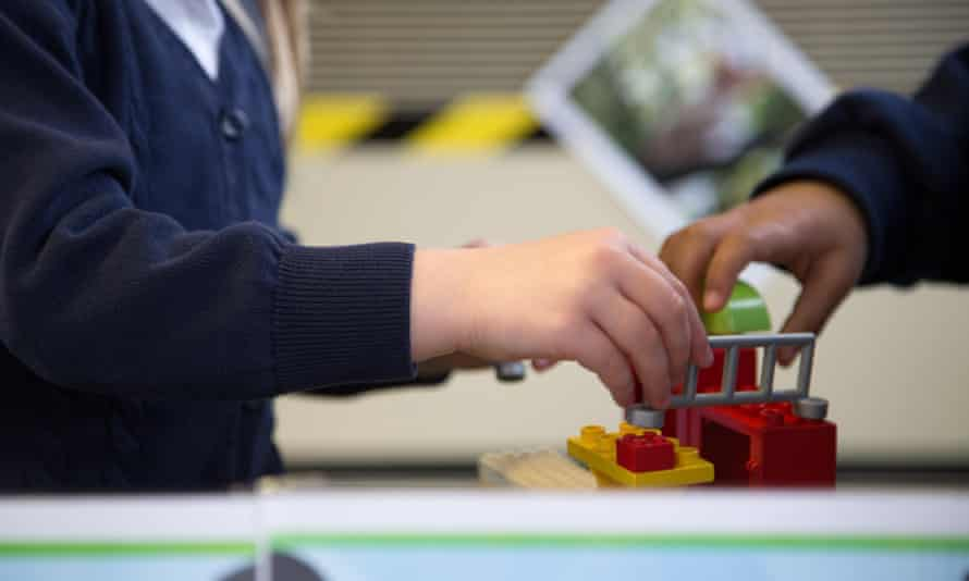 UK primary school children play with lego in a classroom